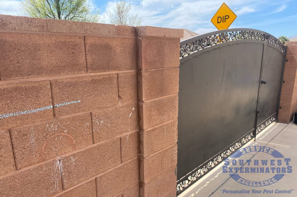 cinder block wall with gate and sign